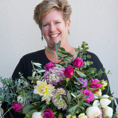 Sandra from Harbour Rose Florist smiling and holding a large bunch of pink and white flowers