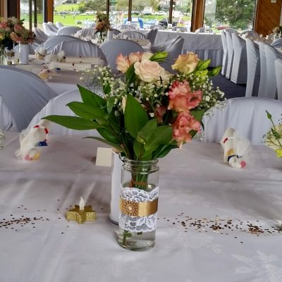 Small flower arrangement in mason jars on table at wedding reception.