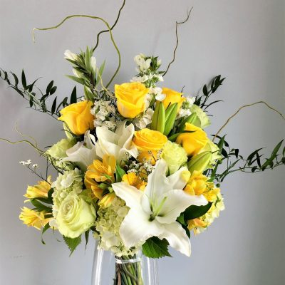 Artistic designer style bouquet with roses, lilies, twisted willow and foliage.