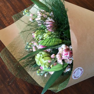 Soft pinks and green flowers in a wrapped bouquet