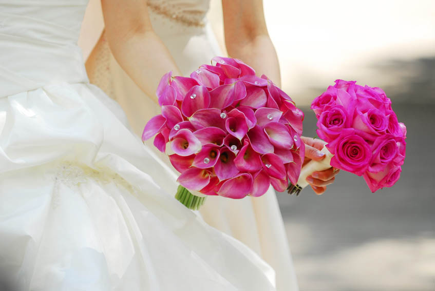 Bride and bridesmaid holding a mass bouquet of pink flowers