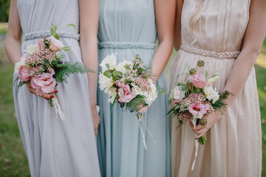 bridesmaid dresses in pastel are holding bouquets in a rustic st
