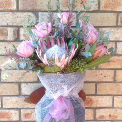 Bouquet of King and Queen proteas with pink O'Hara roses and foliage.