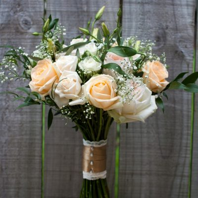 Natural styled Handtied bride's bouquet with stems wrapped in lace and gold ribbon with pearl pins