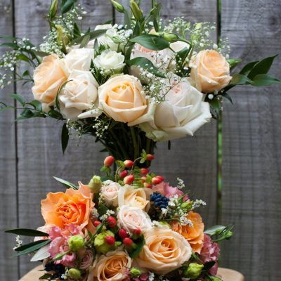 Soft peach bridal bouquet complimented by textural and colourful bridesmaid's bouquet