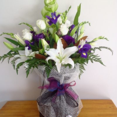 Arrangement of lilies, irises , roses and freesias with foliage in water filled box.