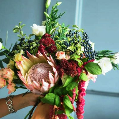 Beautiful rustic bouquet of Lisianthus, roses, King Protea and foliage.