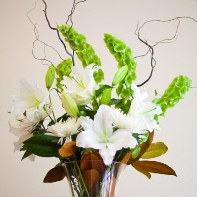 Classi White and Green colour palette of lilies, chrysanthemums and Bells of Ireland with Twisted willow branches.
