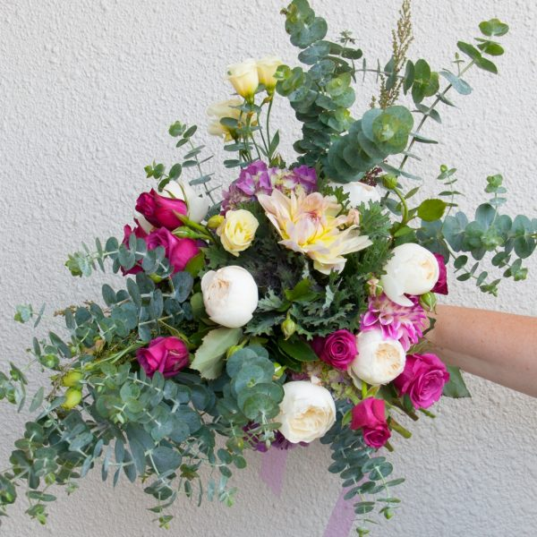 Hand tied bouquet of David Austin roses, dahlias, roses, hydrangeas and lisianthus with eucalyptus foliage.