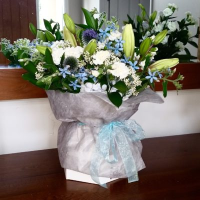 Shades of blue flowers for birthday bouquet in water filled box.