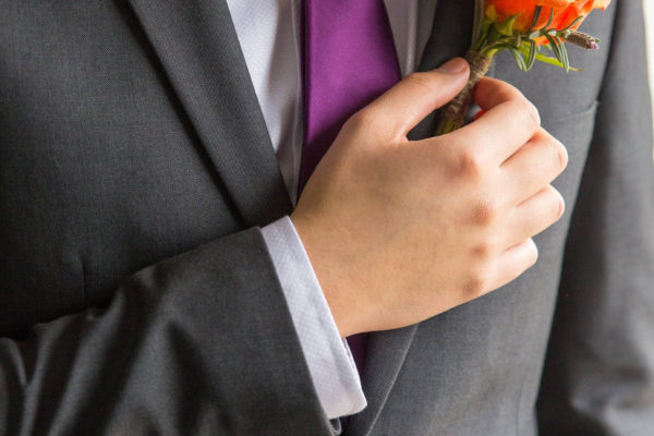 Groom with orange rose buttonhole