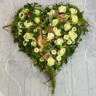 Floral heart tribute of soft pastel flowers and rustic textures