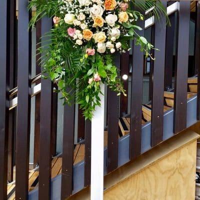 Lush floral arrangement on wedding flower arch