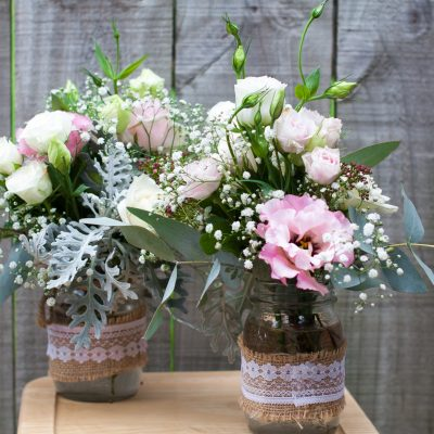 Mason jars full of pastel flowers and foliage