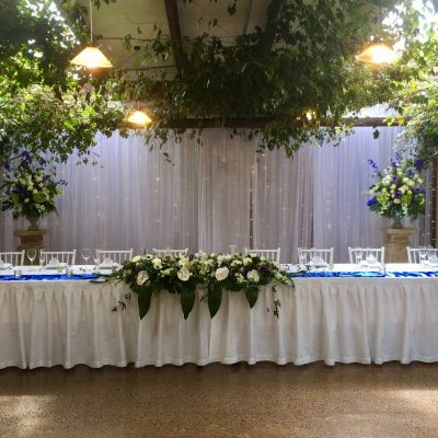 Bridal table with long floral arrangements and pedestal flowers