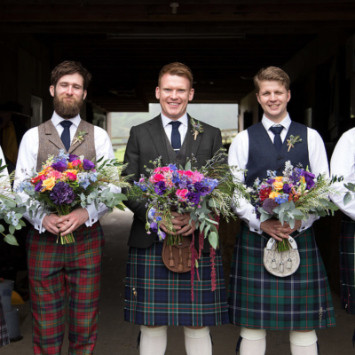 Groom and groomsmen holding garden style wedding bouquets