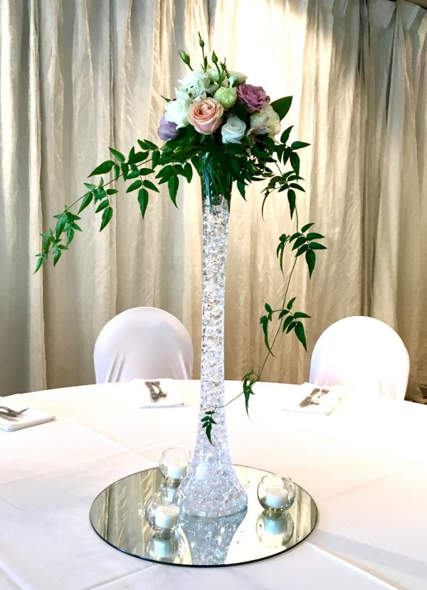Tall vase of wedding flowers on guest table
