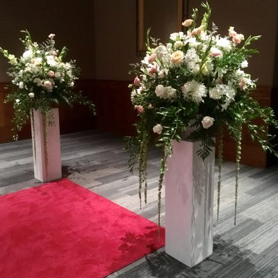 Large wedding floral arrangements on pedestals