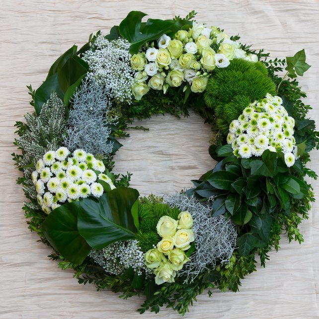 Modern style floral wreath with flower groupings and foliage